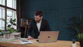 Αρσενικός σχεδιαστής στο γραφείο που λειτουργεί στο lap-top με το πρότυπο σπίτι απόθεμα βίντεο