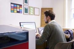 Αρσενικός σχεδιαστής που ενεργοποιεί το σύστημα CAD για τον κόπτη λέιζερ στοκ φωτογραφία