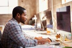 Αρσενικός σχεδιαστής που εργάζεται στο γραφείο στο σύγχρονο γραφείο στοκ φωτογραφίες