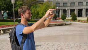Αρσενικός ταξιδιώτης που παίρνει την εικόνα πανοράματος της εικονικής παράστασης πόλης στη συσκευή, θερινές διακοπές φιλμ μικρού μήκους