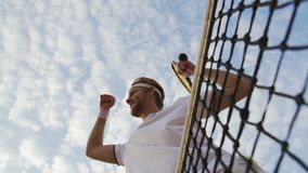 Αρσενικός τενίστας που απολαμβάνει τη νίκη του στο πρωτάθλημα αντισφαίρισης, που αυξάνει τα χέρια απόθεμα βίντεο