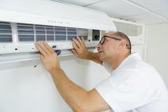 Αρσενικός τεχνικός που ελέγχει το κλιματιστικό μηχάνημα στο σπίτι στοκ εικόνες με δικαίωμα ελεύθερης χρήσης