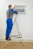 Αρσενικός τεχνικός που επισκευάζει το κλιματιστικό μηχάνημα στοκ φωτογραφία
