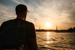 Αρσενικός τουρίστας με ένα σακίδιο πλάτης στο ηλιοβασίλεμα δίπλα στο Bosphorus στη Ιστανμπούλ Η έννοια του ελεύθερου χρόνου, πεζο Στοκ Εικόνες
