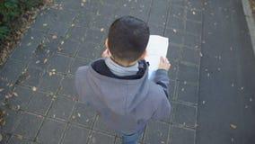 Αρσενικός τουρίστας με το χάρτη πόλεων που περπατά στην οδό, που ψάχνει τα διάσημα ορόσημα απόθεμα βίντεο