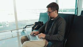 Αρσενικός τουρίστας με το lap-top στον αερολιμένα φιλμ μικρού μήκους