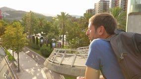 Αρσενικός τουρίστας που απολαμβάνει καταπληκτικός την άποψη μπαλκονιών στη παραθεριστική πόλη, ευτυχής τύπος στις διακοπές απόθεμα βίντεο