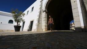 Αρσενικός τουρίστας που εισάγει το προαύλιο, που εμφανίζεται από τη σκοτεινή μετάβαση αψίδων την ηλιόλουστη ημέρα φιλμ μικρού μήκους