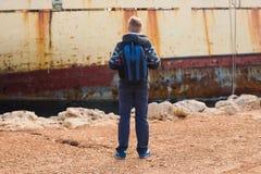 Αρσενικός τουρίστας που εξετάζει ένα εγκαταλειμμένο σκάφος στη θάλασσα ή την ωκεάνια πίσω άποψη Έννοια περιπέτειας και τουρισμού Στοκ Εικόνες