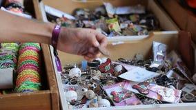 Αρσενικός τουρίστας που επιλέγει το βασικό αναμνηστικό δαχτυλιδιών από το ξύλινο κιβώτιο στην τοπική αγορά οδών απόθεμα βίντεο
