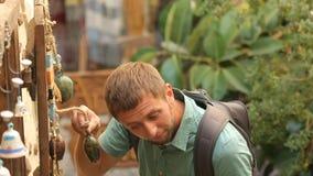 Αρσενικός τουρίστας που στέκεται και που δοκιμάζει τα αναμνηστικά που κρεμούν στη στάση στην οδό, τουρισμός απόθεμα βίντεο
