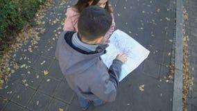 Αρσενικός τουρίστας που ψάχνει τη θέση προορισμού στο χάρτη πόλεων, που ρωτά τον περαστικό για τη βοήθεια φιλμ μικρού μήκους