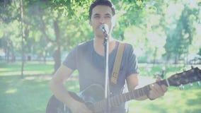 αρσενικός τραγουδιστής Το brunette ατόμων παίζει την κιθάρα και τραγουδά ένα τραγούδι απόθεμα βίντεο