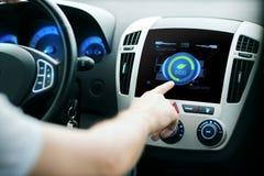 Αρσενικός τρόπος συστημάτων eco αυτοκινήτων χεριών θέτοντας στην οθόνη Στοκ Εικόνες