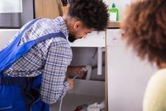 Αρσενικός υδραυλικός που καθαρίζει τους φραγμένους σωλήνες στοκ εικόνες