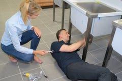 Αρσενικός υδραυλικός στο γενικό σωλήνα νεροχυτών καθορισμού στοκ εικόνες
