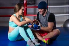 Αρσενικός φίλαθλος μπόξερ που βοηθά να προετοιμάσει το αθλητικό θηλυκό επιδέσμων Στοκ Φωτογραφίες