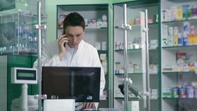 Αρσενικός φαρμακοποιός που επικοινωνεί στο τηλέφωνο στο φαρμακείο απόθεμα βίντεο
