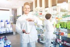 Αρσενικός φαρμακοποιός που φορά το άσπρο παλτό που στέκεται στο φαρμακείο στοκ φωτογραφία με δικαίωμα ελεύθερης χρήσης