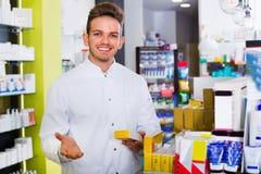 Αρσενικός φαρμακοποιός που φορά το άσπρο παλτό που στέκεται στο φαρμακείο στοκ φωτογραφίες με δικαίωμα ελεύθερης χρήσης