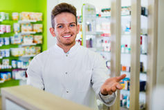 Αρσενικός φαρμακοποιός που φορά το άσπρο παλτό που στέκεται στο φαρμακείο στοκ εικόνες