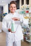 Αρσενικός φαρμακοποιός που φορά το άσπρο παλτό που στέκεται στο φαρμακείο στοκ εικόνες με δικαίωμα ελεύθερης χρήσης
