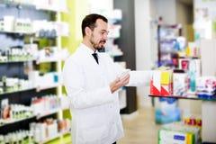 Αρσενικός φαρμακοποιός που ψάχνει για το αξιόπιστο φάρμακο στοκ φωτογραφίες