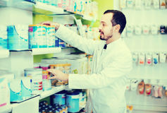 Αρσενικός φαρμακοποιός που ψάχνει τη σωστή ιατρική στο φαρμακείο στοκ φωτογραφία με δικαίωμα ελεύθερης χρήσης