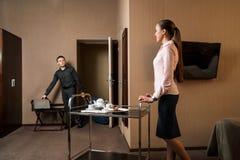 Αρσενικός φιλοξενούμενος με τη βαλίτσα που μπαίνει σε το δωμάτιο ξενοδοχείου στοκ εικόνα
