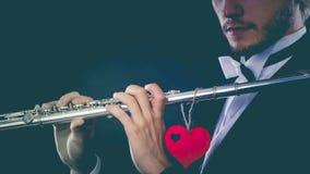 Αρσενικός φλαουτίστας με το φλάουτο και την καρδιά Μελωδία αγάπης στοκ εικόνα