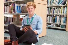 Αρσενικός φοιτητής πανεπιστημίου που μελετά στη βιβλιοθήκη με την ψηφιακή ταμπλέτα Στοκ Φωτογραφίες