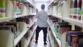 Αρσενικός φοιτητής πανεπιστημίου που χορεύει στη βιβλιοθήκη απόθεμα βίντεο