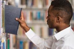 Αρσενικός φοιτητής πανεπιστημίου σε μια βιβλιοθήκη Στοκ Φωτογραφία