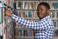 Αρσενικός φοιτητής πανεπιστημίου σε μια βιβλιοθήκη Στοκ Εικόνα