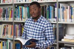 Αρσενικός φοιτητής πανεπιστημίου σε μια βιβλιοθήκη Στοκ Φωτογραφίες