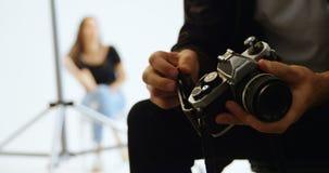 Αρσενικός φωτογράφος που βάζει την ταινία ρόλων κεκλεισμένων των θυρών 4k φιλμ μικρού μήκους