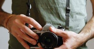 Αρσενικός φωτογράφος που στέκεται με τη ψηφιακή κάμερα στο στούντιο φωτογραφιών 4k απόθεμα βίντεο