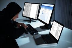 Αρσενικός χάκερ που χρησιμοποιεί τους υπολογιστές Στοκ φωτογραφία με δικαίωμα ελεύθερης χρήσης