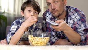 Αρσενικός χρόνος εξόδων επιχείρησης που προσέχει μαζί τη TV και που τρώει popcorn, πατρότητα στοκ φωτογραφία με δικαίωμα ελεύθερης χρήσης