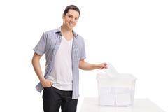 Αρσενικός ψηφοφόρος που πετά μια ψηφοφορία σε ένα κάλπη Στοκ εικόνα με δικαίωμα ελεύθερης χρήσης