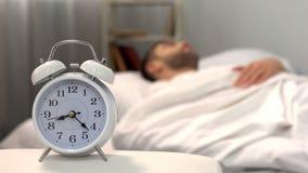 Αρσενικός ύπνος στο κρεβάτι, άσπρο ξυπνητήρι που στέκεται στο επιτραπέζιο πρωί, biorhythm στοκ φωτογραφίες