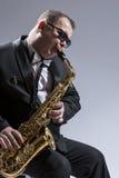 Αρσενικός ώριμος φορέας Saxophone στα γυαλιά ηλίου που παίζει το Saxophone Στοκ φωτογραφία με δικαίωμα ελεύθερης χρήσης