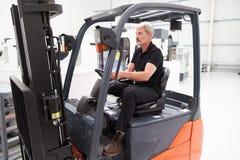 Αρσενικός forklift οδηγός φορτηγού που εργάζεται στο εργοστάσιο Στοκ φωτογραφία με δικαίωμα ελεύθερης χρήσης
