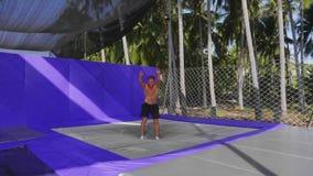 Αρσενικός gymnast εκπαιδεύει στο τραμπολίνο υπαίθριο στο υπόβαθρο φοινίκων φιλμ μικρού μήκους