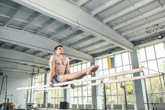 Αρσενικός gymnast που αποδίδει handstand στους παράλληλους φραγμούς Στοκ Εικόνα