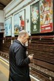 Αρσενικό άτομο που χρησιμοποιεί το τηλέφωνο smartphone iPhone στο σωλήνα του Λονδίνου underg Στοκ Εικόνα