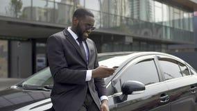 Αρσενικό άτομο στο ακριβό κοστούμι που περιμένει το σύντροφο, να τυλίξει ειδήσεις στη συσκευή απόθεμα βίντεο