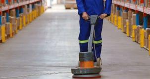 Αρσενικό αποθηκών εμπορευμάτων πάτωμα αποθηκών εμπορευμάτων εργαζομένων καθαρίζοντας απόθεμα βίντεο