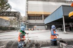 Αρσενικό ασιατικό laborer με τα λύματα φτυαριών cleanout στον υπόνομο στο εργοστάσιο τσιμέντου Έννοια σκληρής δουλειάς στοκ φωτογραφία με δικαίωμα ελεύθερης χρήσης