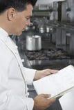 Αρσενικό βιβλίο συνταγής ανάγνωσης αρχιμαγείρων στην κουζίνα Στοκ Εικόνες